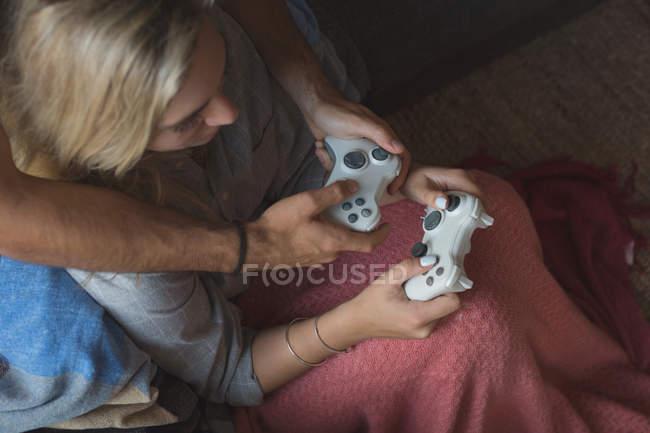Пара, играющая в видеоигры в гостиной дома — стоковое фото