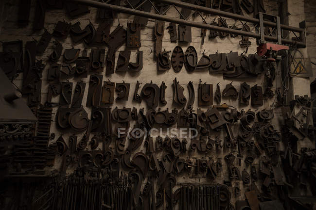 Various metal pieces hanging in workshop — Stock Photo