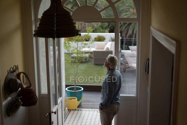 Homme âgé réfléchi debout près de la porte à la maison — Photo de stock