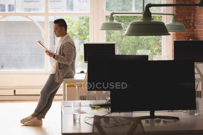 Male executive sitting on table reading documents in the office — Stock Photo