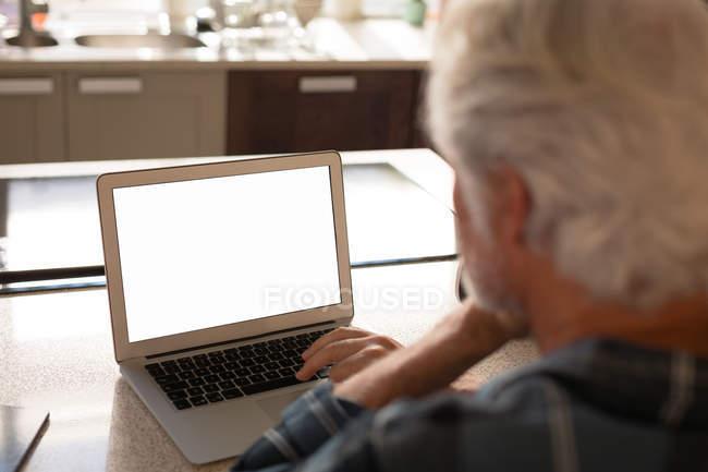 Senior benutzte Laptop in Küche zu Hause — Stockfoto