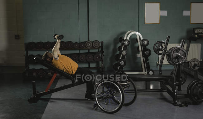 Handicapped man exercising with dumbbells on bench press in gym — Stock Photo