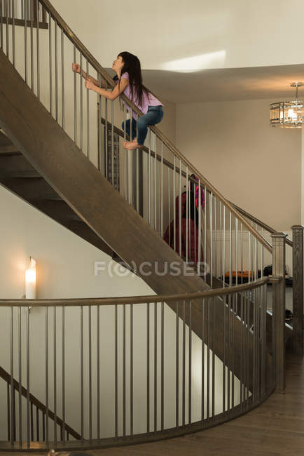 Happy girl playing on staircase railing at home — Stock Photo