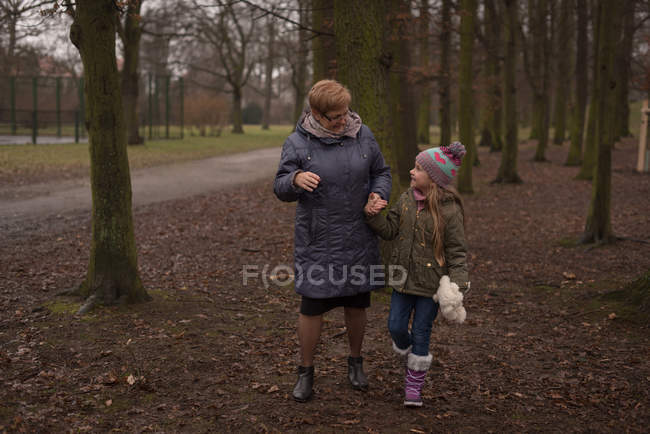 Grandmother and granddaughter interacting with each other in forest — Stock Photo
