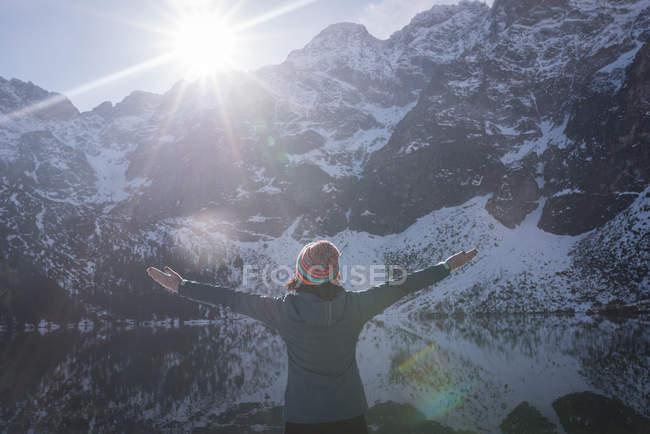 Жіночий мандрівного, стоячи з руки схрещених під lakeside взимку — стокове фото