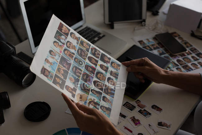Female graphic designer holding photograph in the office — Stock Photo