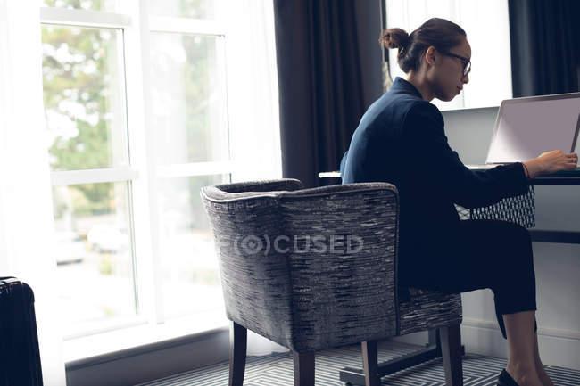 Жінка, використовуючи ноутбук на стіл в готельному номері — стокове фото