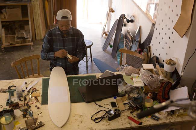Чоловік біля скейтборд в майстерні, вигляд згори — стокове фото