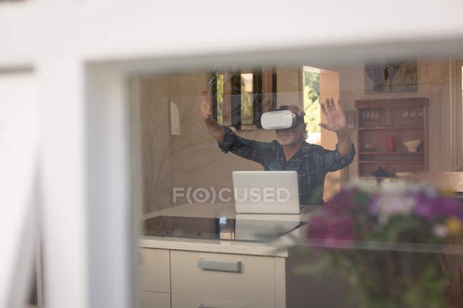Senior man using virtual reality headset with laptop in kitchen at home — Stock Photo