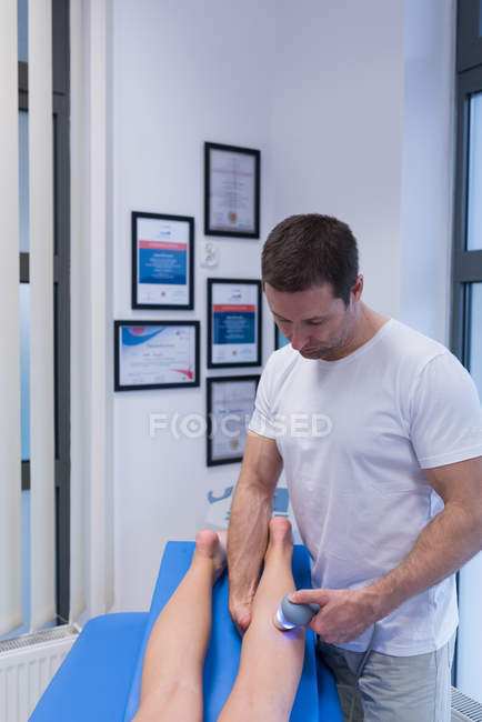 Physiotherapist giving leg massage to woman with machine in clinic — Stock Photo