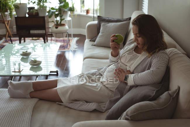 Беременная женщина отдыхает на диване в гостиной на дому — стоковое фото
