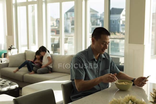 Отец, имея завтрак и девочек на дому с использованием цифрового планшета — стоковое фото