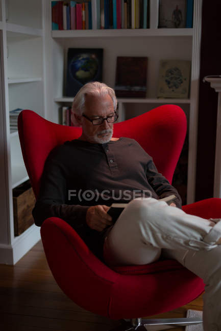 Senior man reading a book in living room — Stock Photo