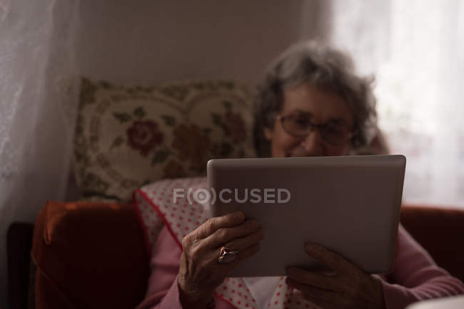 Active senior woman using digital tablet at home — Stock Photo
