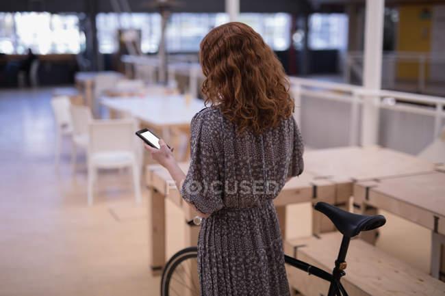 Vue arrière du général femelle à l'aide de téléphone portable au bureau — Photo de stock