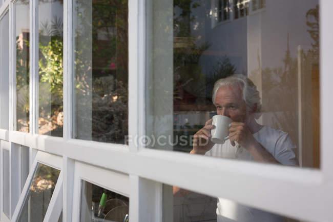 Senior man having coffee in kitchen at home — Stock Photo