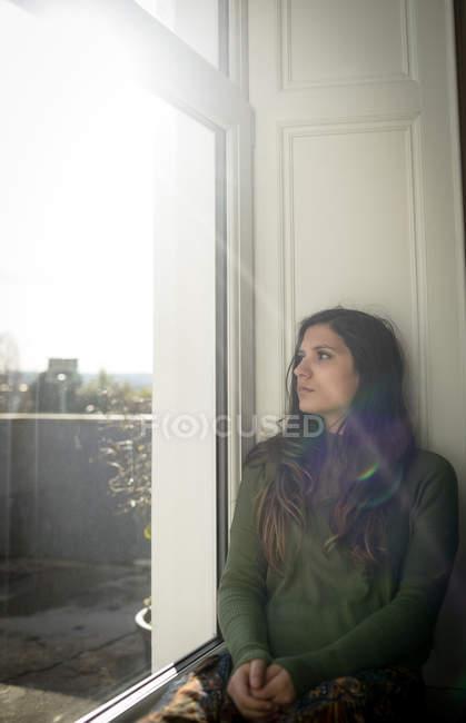 Ragionevole donna guardando attraverso la finestra mentre seduto sul davanzale della finestra a casa — Foto stock