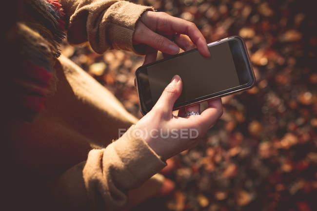 Section médiane de la femme à l'aide de téléphones mobiles au cours de l'automne — Photo de stock