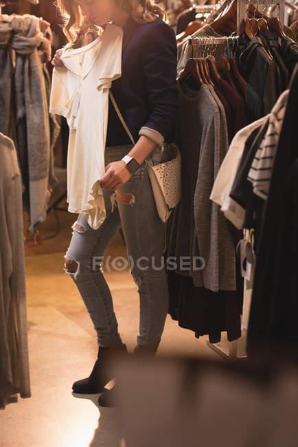 Menina bonita verificando o vestido no shopping — Fotografia de Stock