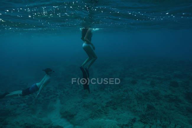 Couple plongée sous-marine en mer turquoise — Photo de stock