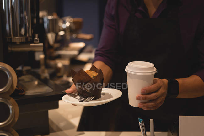 Mid section of waiter serving coffee and muffin in plate at coffee shop — Stock Photo