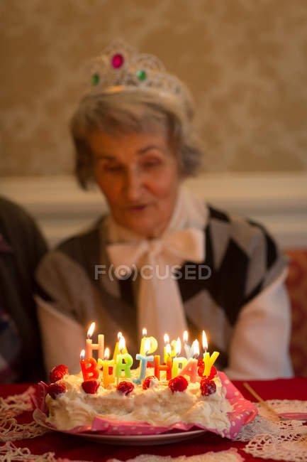 Senior Woman Blowing Out Candles On Birthday Cake At Home One Person Citizen
