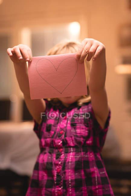 Девушка, держащая украшение в форме сердца дома — стоковое фото