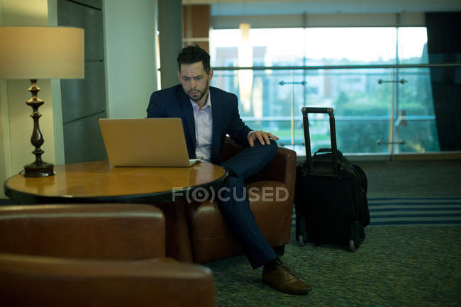 Businessman using laptop in hotel — Stock Photo