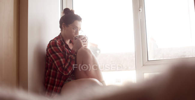 Thoughtful woman drinking coffee on window sill at home. — Stock Photo