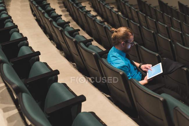 Redhead man using digital tablet on theatre seat. — Stock Photo