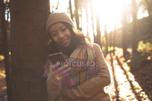 Женщина в теплой одежде с помощью мобильного телефона в лесу — стоковое фото