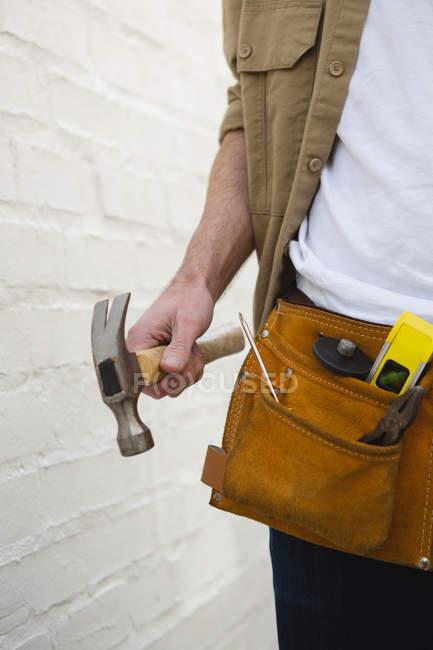 Розділ середині чоловічого Карпентер з інструмент пояса проведення молоток — стокове фото