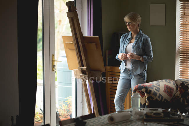 Female artist observing painting on canvas at home — Stock Photo