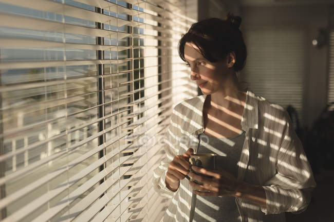 Jovem mulher segurando a caneca de café, olhando pela janela em casa — Fotografia de Stock