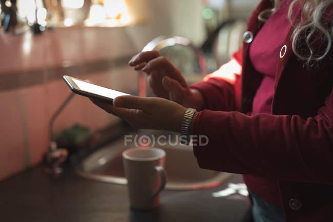 Seção média de mulher madura usando tablet digital na cozinha — Fotografia de Stock