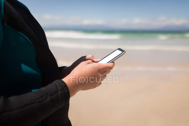 Mid section of girl in wetsuit using mobile phone on beach — Stock Photo