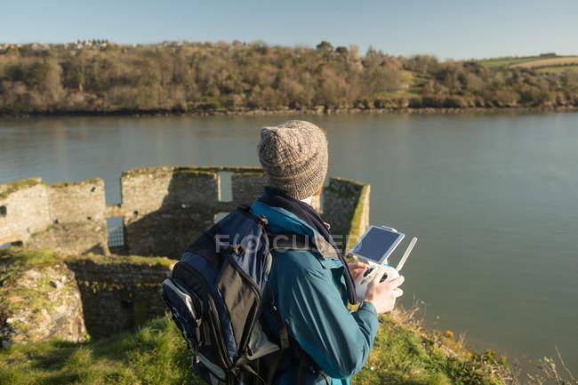 Vue arrière d'un randonneur qui utilise un drone près d'un lac à la campagne — Photo de stock