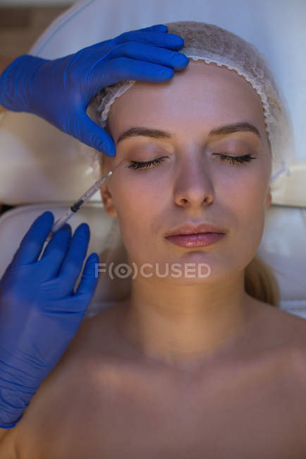 Beautician giving beauty treatment to female customer in parlour — Stock Photo
