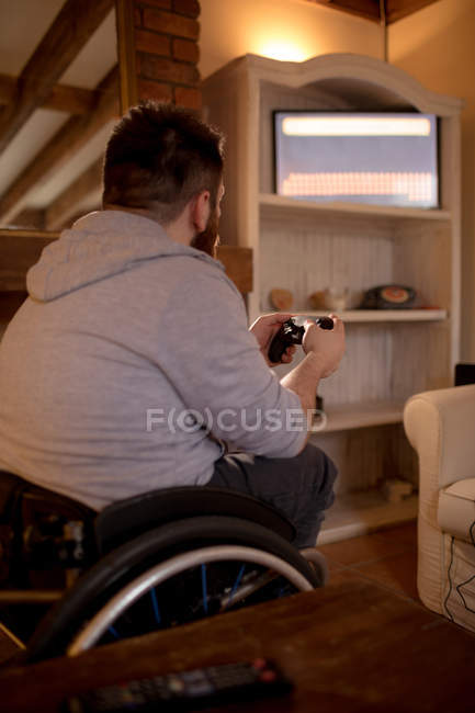 Disabled man playing video games at home — Stock Photo