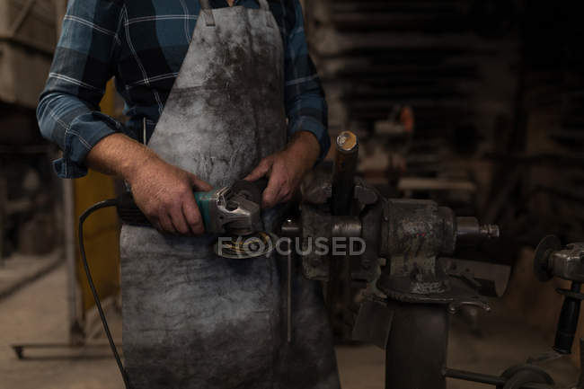 Blacksmith grinding a metal rod with grinder machine in workshop — Stock Photo