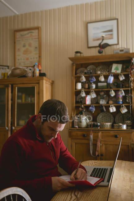 Hombre escribiendo en un libro mientras usa el ordenador portátil en casa - foto de stock