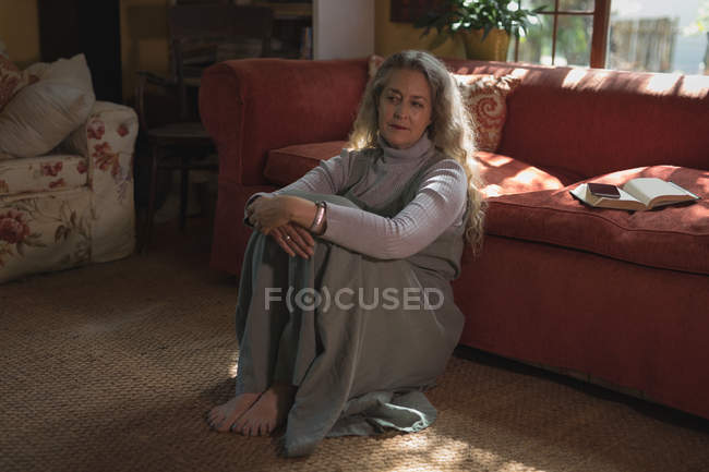 Задумчивая зрелая женщина сидит дома на земле — стоковое фото