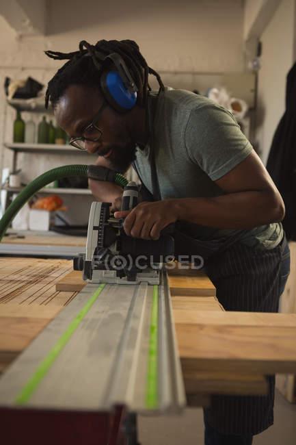 Плотник выравнивания древесины с полировальная машина в мастерской — стоковое фото