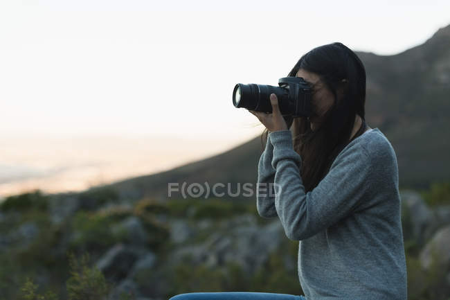 Woman clicking photo with a camera at dusk — Stock Photo