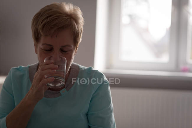 Senior woman having glass of water at home — Stock Photo