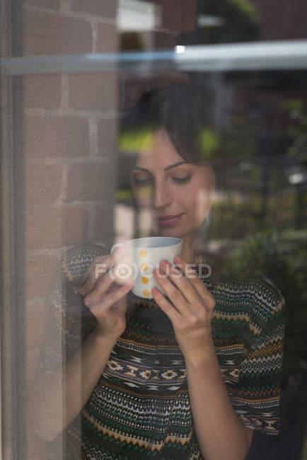 Молодая женщина-руководитель пьет кофе в офисе — стоковое фото