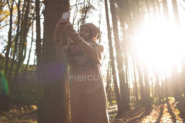 Femme prenant selfie avec téléphone portable à la forêt — Photo de stock