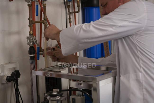 Рабочий мужчина осматривает джин в измерительном цилиндре на заводе — стоковое фото