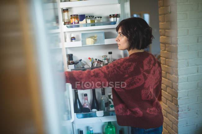 Mujer joven mirando en el refrigerador en casa - foto de stock
