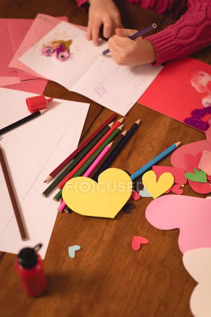 Fille dessin sur carte de Saint-Valentin à la maison — Photo de stock